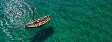 Aerial Drone Ultra Wide Photo Of Beautiful Wooden Deck Small Classic Sailing Yacht Anchored In Emerald Sea