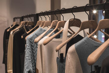 Coat And Sweater Light Brown And Gray Colors On The Hanger In The Store. Classic Women's Fashion Clothes.