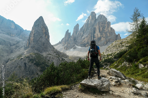 Obraz A man with big backpack hiking in high, Italian Dolomites. There are many sharp peaks behind. He is standing on a big boulder, enjoying the view. There are a few trees around. Sunny day. Outdoor - fototapety do salonu