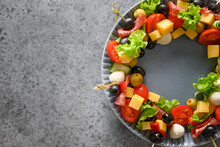 Christmas Wreath Of Snacks, Canapes, Tomatoes, Vegetables, Mozzarella Cheese For Festive Xmas Party On Grey Background. Copy Space. View From Above.