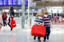 Two Little Sibling Boys Wear Medical Mask And Going On Vacations Trip With Suitcase At Airport, Indoors. Happy Twins Brothers Walking To Check-in Or Boarding For Flight During Corona Virus Pandemic