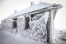 Snow Covered Frozen Hut In Mountains In Winter