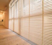 Motorized Wood Blinds In The Interior. Automatic Venetian Blinds Beige Color On Large Windows. Coulisse Wooden Slats 50mm Wide. Wood Floor, Beige Walls.