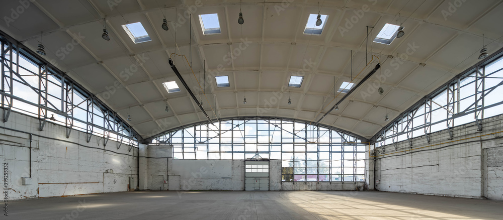 Fototapeta Huge empty industrial warehouse. White interior. Unique architecture. Hemispherical reinforced concrete load bearing roof with windows. Modern building.