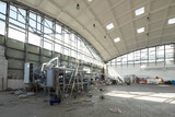 Fototapeta Przestrzenne - Heavy equipment in uge industrial warehouse.  Unique architecture. Hemispherical reinforced concrete load bearing roof with windows.
