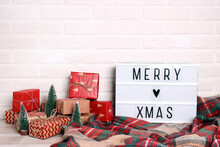 Merry Xmas Text On White Lightbox With Miniature Christmas Trees,heap Of Wrapped Gifts And Checkered Plaid Against White Brick Wall.