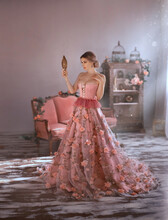 Beautiful Woman In Sexy Long Medieval Pink Dress, Spring Flowers On Skirt, Looks At Herself. Holds In Hand Vintage Mirror. Adult Girl Queen With Big Breasts In Corset, Open Chest. Elegant Bun Hair