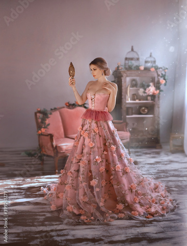 Stampa su Tela beautiful woman in sexy long medieval pink dress, spring flowers on skirt, looks at herself