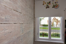 Room With Wooden Wall And Window And Patterned Window Blind.