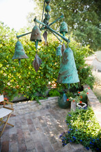 Wind Chime Or Mobile With Bronze Bells Hanging Over Garden Terrace.
