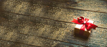 Christmas Background - Gift Box With Red Bow On Wooden Board With Festive Golden Glitter