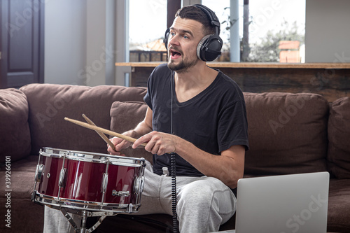 Photo A young man with headphones learns to play the drum using online lessons