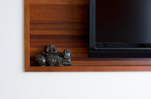 Buddha Statue On Shelf With TV.