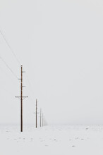 Power Lines In Snowy Wintry Landscape With Grey Sky.