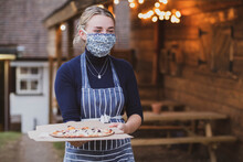 Woman Waitress In Apron And Face Mask Holding Plate Of Pizza.