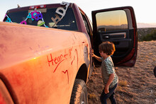 Young Boy Writing On Paint On An Old Pickup Truck