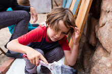 Seven Year Old Boy Using A Paintbrush, Painting Cardboard