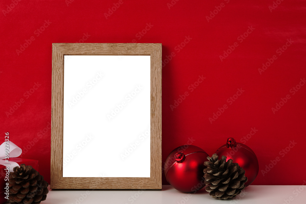 Fototapeta Blank wooden photo frame mockup template and christmas decoration on red blackground.