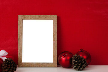 Blank wooden photo frame mockup template and christmas decoration on red blackground.