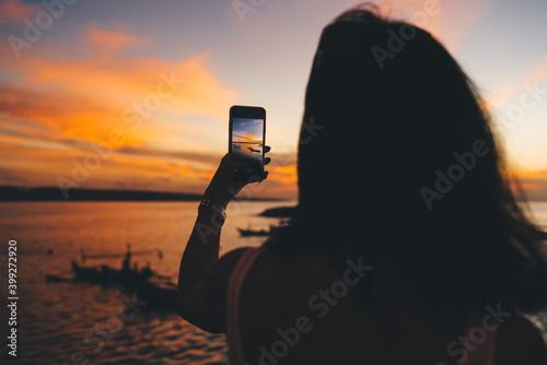 Fototapeta Faceless woman shooting sky with smartphone on seafront obraz
