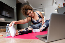 Young Plus Size Woman At Home Doing Exercise In Front Of Open Laptop, Repeating Instructions By Professional Online Fitness Trainer.