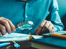 The Auditor Checks The Accounting Records And Reports With A Magnifying Glass.