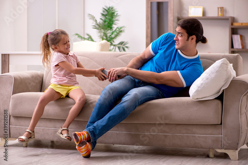 Fototapeta Young man with his daughter at home obraz