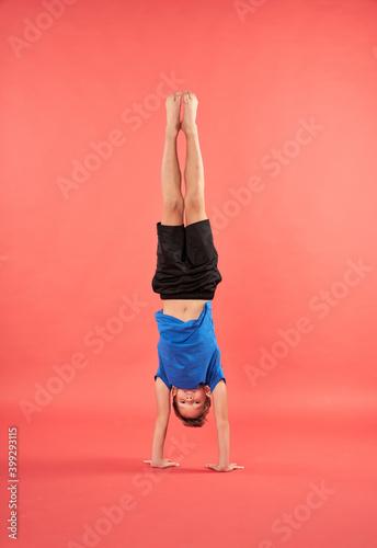 Obraz na plátně Adorable male child in sportswear doing handstand exercise