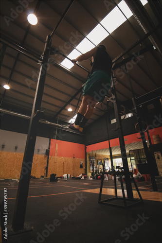athlete doing pull-up in gym