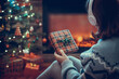 Woman in headphones with christmas gift box in hand sitting on fluffy plaid near fireplace and christmas tree.