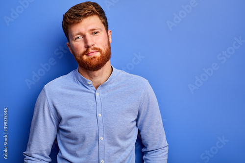 Fotografie, Obraz intelligent guy in shirt posing at camera isolated over blue background, handsom