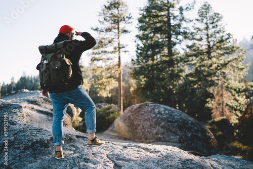 Unrecognizable man with backpack standing on rock