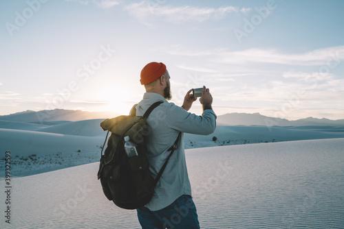 Faceless bearded man resting on sandy hill