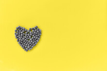 Heart From Green Peas Of Gray Flowers On A Yellow Background. Showcasing The Trendy Colors Of 2021 - Gray And Yellow. Place For An Inscription. View From Above.