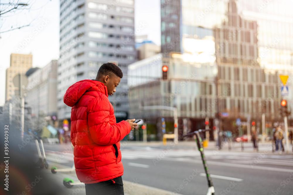 Fototapeta Young man using smart phone outdoors at urban setting
