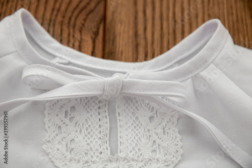 Foto Collar with a tied bow on a christening shirt for a child on a wooden background close-up
