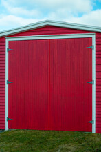 A Large Vintage Red Wooden Garage Door With White Trim.  The Tall Doors Are Closed And Have Three Hinges On Both Sides. The Background Is A Blue Sky With Clouds. The Ground Is Covered In Green Grass.