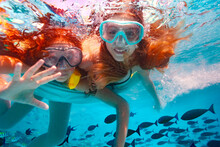 Two Beautiful Girls In Scuba Mask Swim Underwater And Wave Hand To The Camera Smiling In The Pool