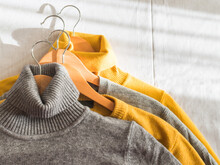 Yellow Illuminated Color And Gray Winter Sweaters On Wooden Hangers. Trendy Fashion Autumn Warm And Cozy Clothes. Top View