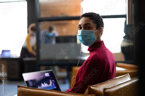 Portrait of mixed race woman wearing face mask working on laptop wearing earphones in casual office