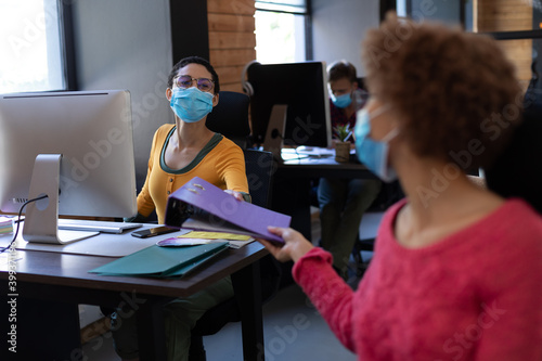 Diverse female colleagues wearing face masks passing file between desks