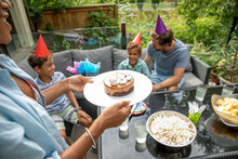 Family Wearing Cone Hats Celebrating Boy's Birthday On Terrace