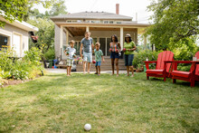 Family Playing Lawn Bowl In Backyard