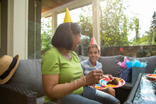 Woman And Grandson Talking And Having Birthday Cake On Sofa