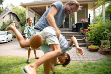Man Tackling Son At Soccer Game In Backyard