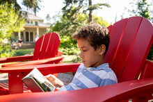 Portrait Of Boy Reading Book On Red Garden Chair