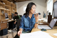 Designer In Architecture Firm Talking Through Plans On Phone
