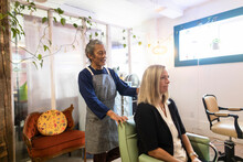 Hairdresser Giving Hairstyling Advice To Customer