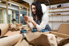 Owner Of Ceramics Business Startup Texting On Phone