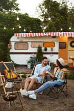 Happy Couple With Burgers And Beer Resting Near Trailer. Camping Season